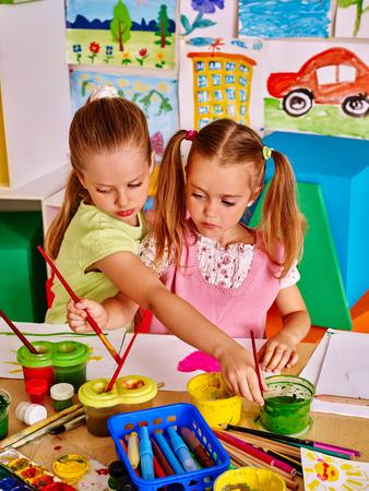 niño escuela: Niños pintura de la muchacha a la mesa en la escuela infantil. Foto de archivo