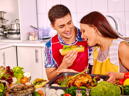 Happy young couple cooking chicken at kitchen indoor. photo