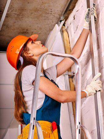 foremaster: Happy woman in builder uniform and helmet  indoor.