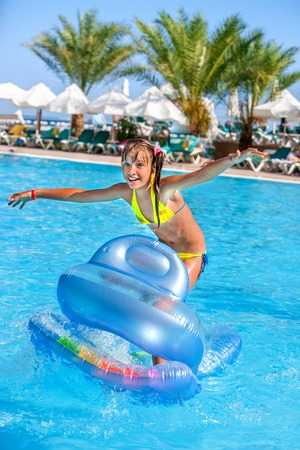 little girl smiling: Little girl swimming on inflatable beach mattress. Stock Photo