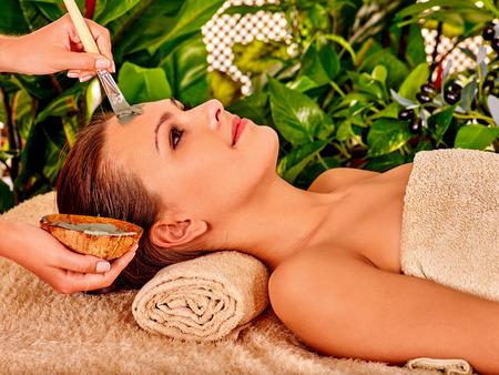 masajes faciales: Mujer con máscara facial de arcilla en el spa de belleza.