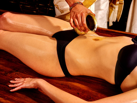 woman chest: Young woman having stomach Ayurveda spa treatment. Stock Photo