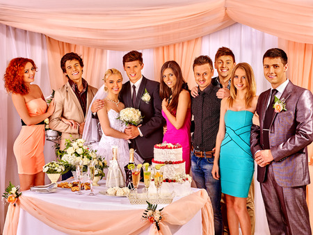 Happy wedding couple and guests drinking champagne. photo