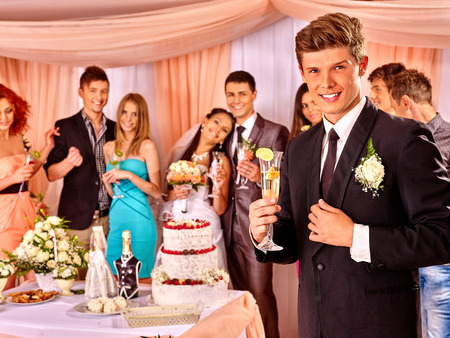 party food: Group people at wedding table with cake.