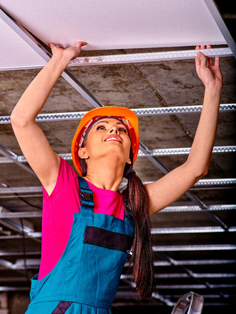 renovating: Woman in builder uniform installing suspended ceiling