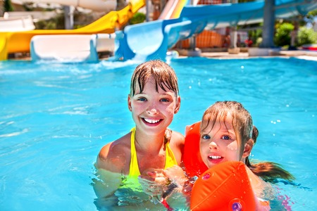 armbands: Children with armbands in swimming pool on water park. Stock Photo