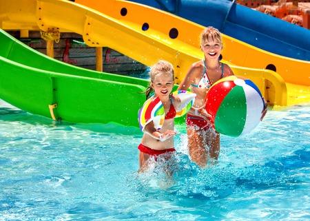 beach ball girl: Little girl kids playing beach ball in swimming pool.