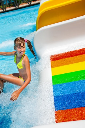 summer holiday bikini: Happy kid little girl in yellow bikini sliding water park.