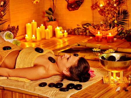 stone therapy: Woman getting stone therapy massage in bamboo spa. Stone therapy with burning candle.