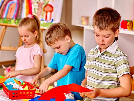 preschool classroom: Group of children  in preschool scissors cut paper. Stock Photo
