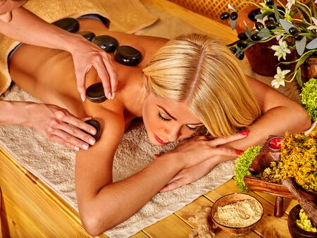 stone therapy: Young woman getting relaxing hot stone therapy massage .