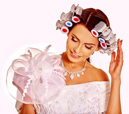 head wear: Donna con i bigodini in testa indossare in abito da sposa su isolato.