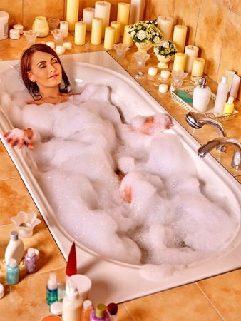 Woman relaxing at water in bubble bath. Top view. Standard-Bild
