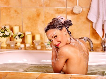 mujer bañandose: La mujer lava su cabeza al baño casa. El agua en el baño.