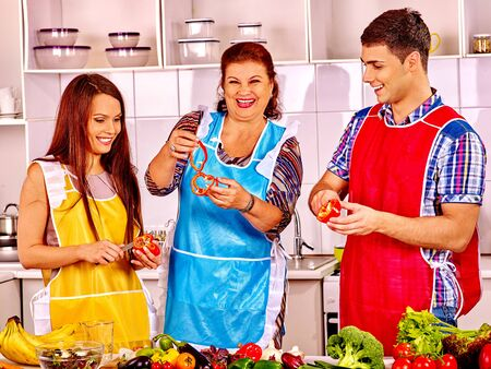 family dinner: Mature woman with young happy family preparing  dinner at kitchen. Stock Photo