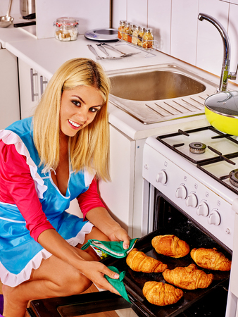 bap: Young woman bake cookies in stove in kitchen. Stock Photo