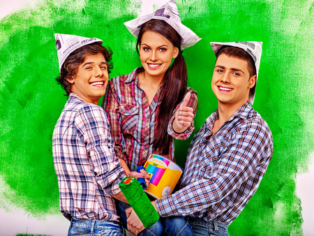 one woman: Happy group people two men and one woman paint wall at home. Stock Photo