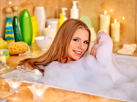 woman in bath: Happy smiling woman  taking bath with a lot of foam. Stock Photo