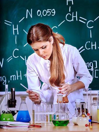 testtube: Chemistry female teacher with test-tube at classroom and green blackboard.