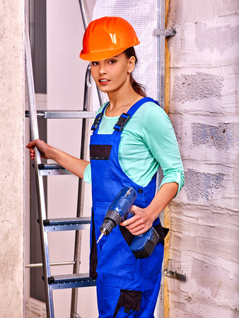Yong woman in blue builder uniform indoor. photo