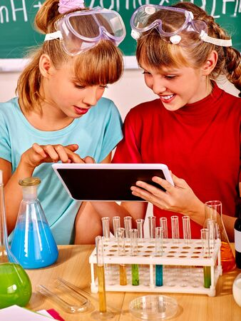 science lesson: Child holding tablet pc in chemistry class. Stock Photo