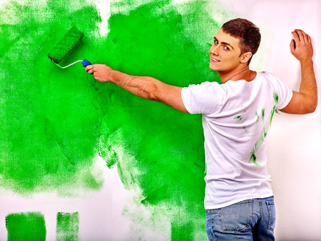 decoration messy: Happy man paint wall at home.