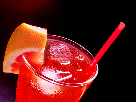 dark cherry: Red  drink  with cherry and pineapple in highball glass . Top view.