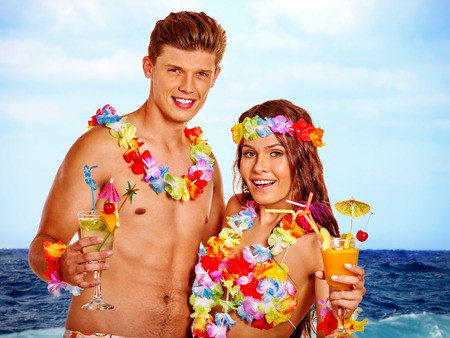 Couple with cocktail at Hawaii wreath beach. Summer outdoor. Stock Photo
