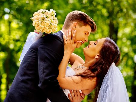 happy wedding: Happy wedding couple kissing bride outdoor.