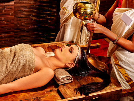 Young woman having pouring oil Ayurveda spa treatment. Stock Photo