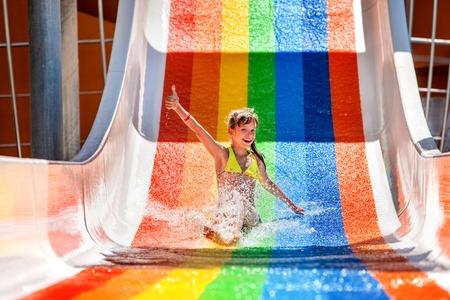 Happy child girl in bikini sliding water park. Imagens
