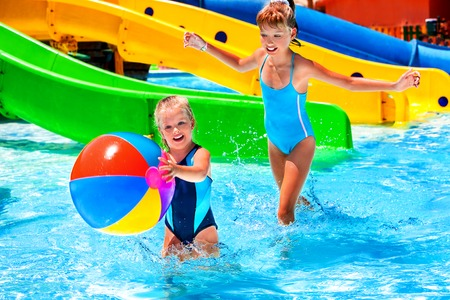 kids swimming pool: Little girl on water slide at aquapark. Stock Photo