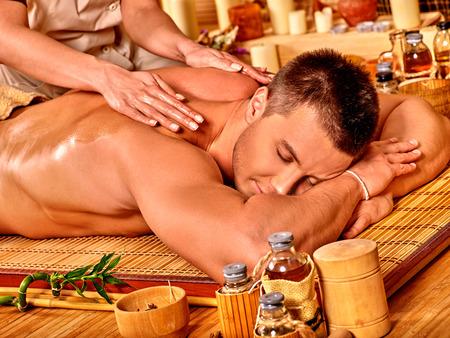 masajes relajacion: Hombre recibiendo masajes en el spa de bambú. Terapeuta Mujer.