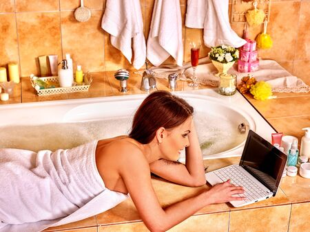 lying in bathtub: Woman relaxing at home luxury bath with laptop.