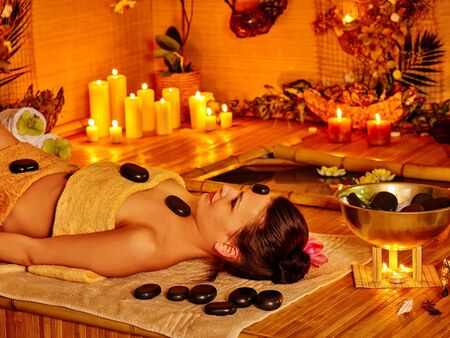 stone therapy: Woman getting stone therapy massage in bamboo spa.