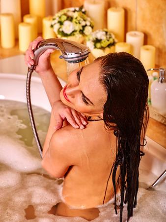 mujer bañandose: La mujer lava su cabeza al baño casa.