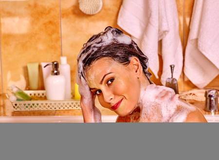 vaporarium: Happy woman washing hair in bubble bath.