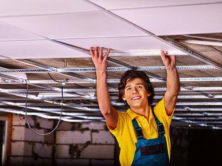 home lighting: Man in builder uniform installing suspended ceiling