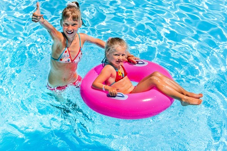 float tube: Children sitting on inflatable ring in swimming pool. Stock Photo