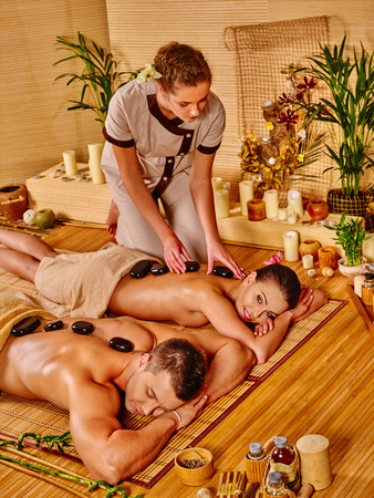 stone therapy: Woman and man getting stone therapy massage in bamboo spa. Stock Photo