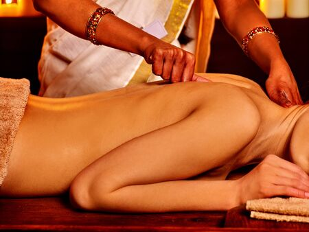 panchakarma: Young woman having oil Ayurveda spa treatment. Bare back and Indian hands.