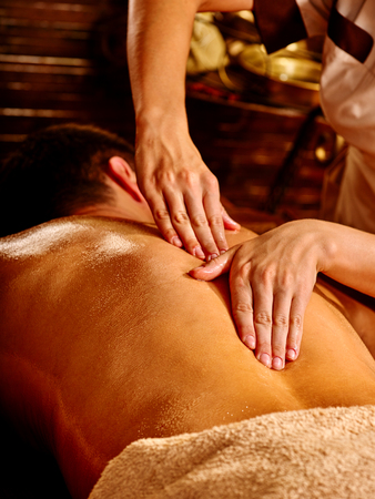 panchakarma: Man  having oil Ayurveda spa treatment. Male back close up.