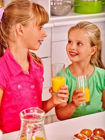 ni�os desayuno: los ni�os el desayuno feliz de zumo de naranja en la cocina. Foto de archivo