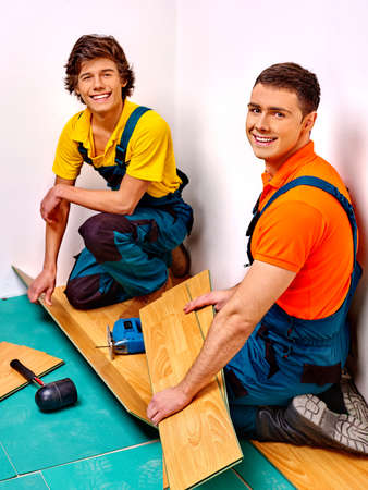 laminate flooring: Happy two men laying parquet at home.