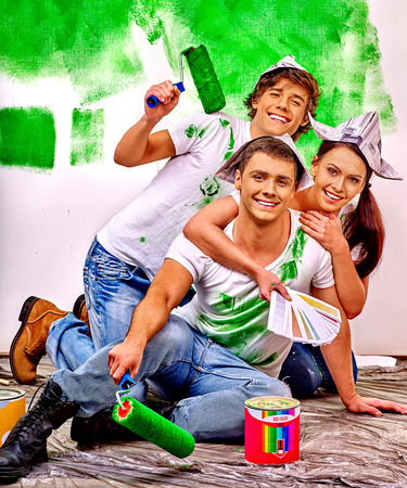 happy group: Happy group people of three person paint wall at home. Stock Photo