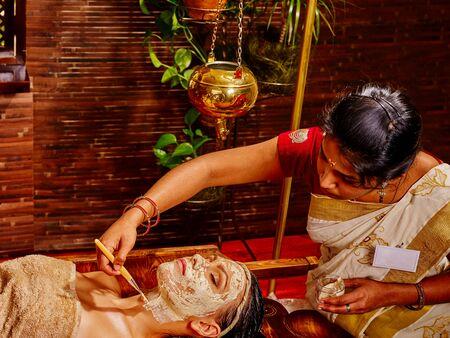 masaje facial: Mujer que tiene máscara facial de arcilla de la India en el spa ayurveda. Foto de archivo