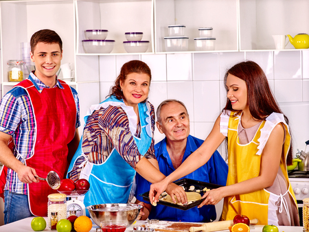 two generations: Happy senior family with adult children cooking at kitchen. Two generations.