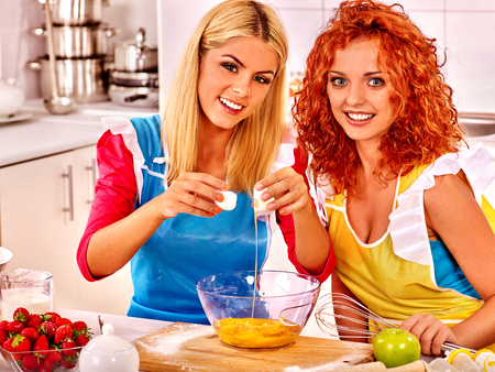 PRETTY WOMEN: Young women  baking cookies in oven together. Stock Photo