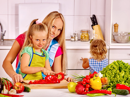 home cooking: Mother and daughter cooking vegetarian food at kitchen. Stock Photo