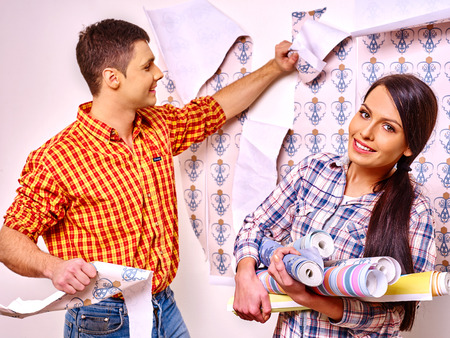 decorate: Happy family glues colors wallpaper at home. Stock Photo